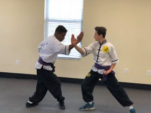 two students practicing martial arts for reduced aggression